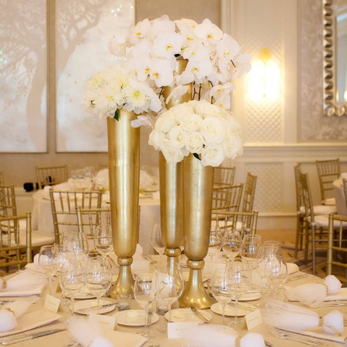 Gold Vases With Lush White Blooms Decorate Each Reception Table