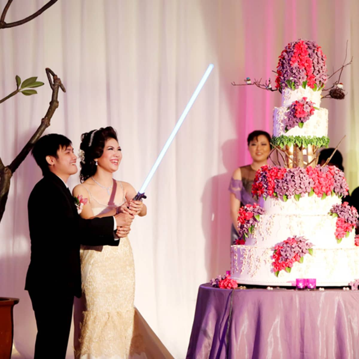 The couple use a Jedi lightsabre to cut their wedding cake.