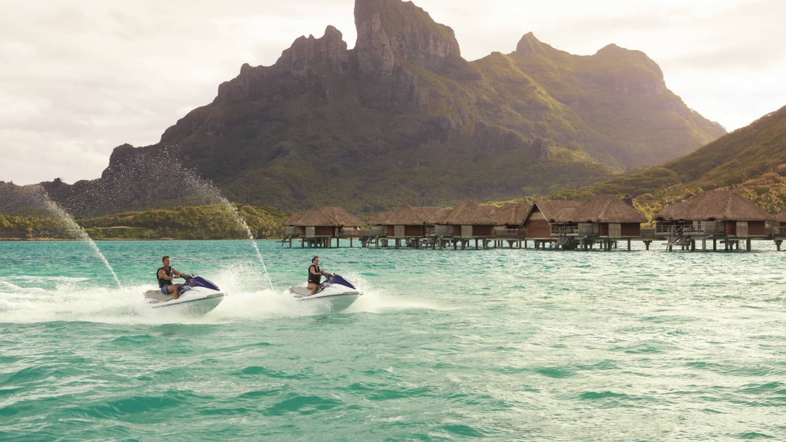Two jet skis ride along lagoon past row of overwater bungalows, Bora Bora mountain