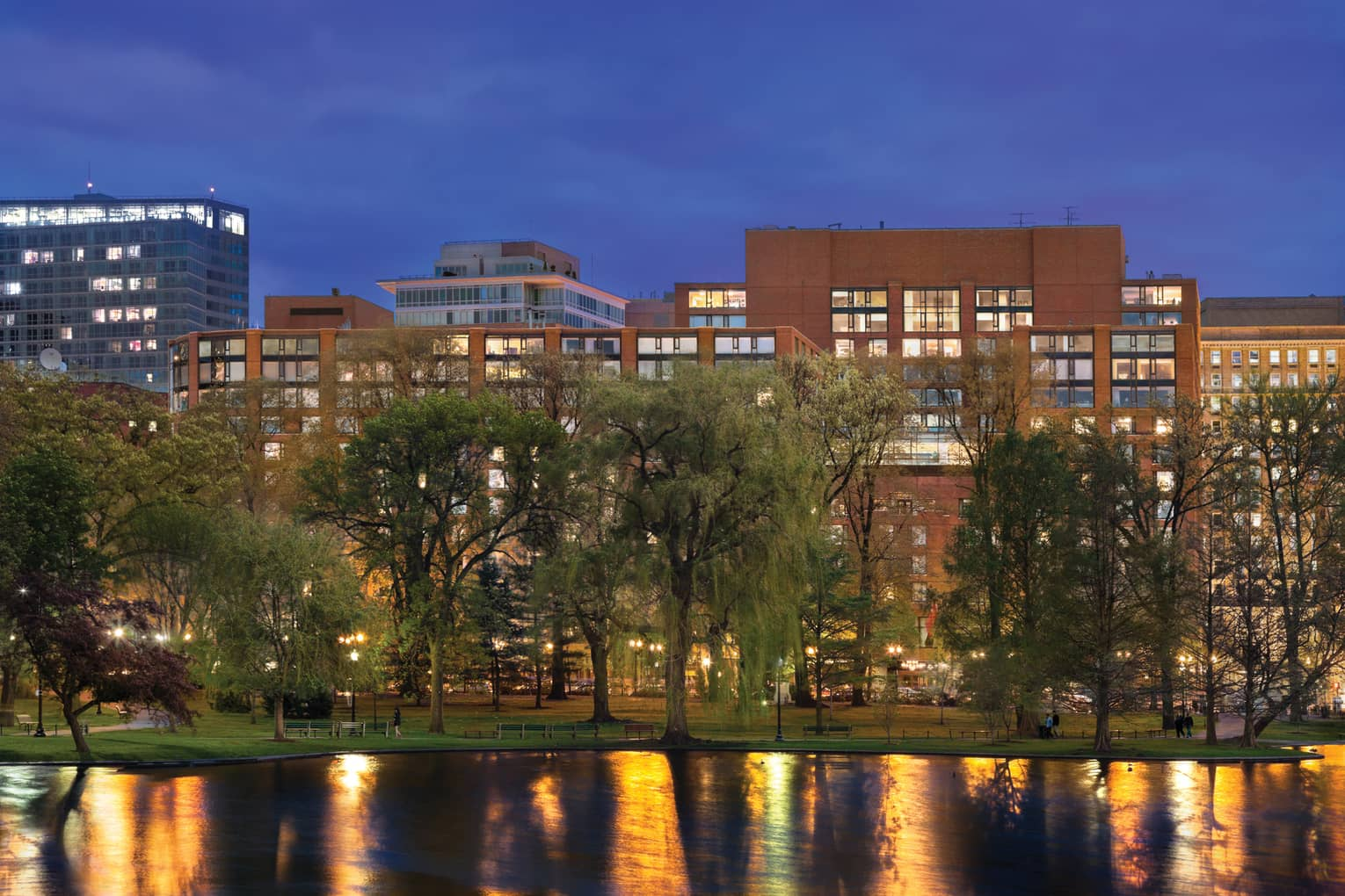 Exterior view of hotel at dusk with tall green trees and pond in Boston Public Garden