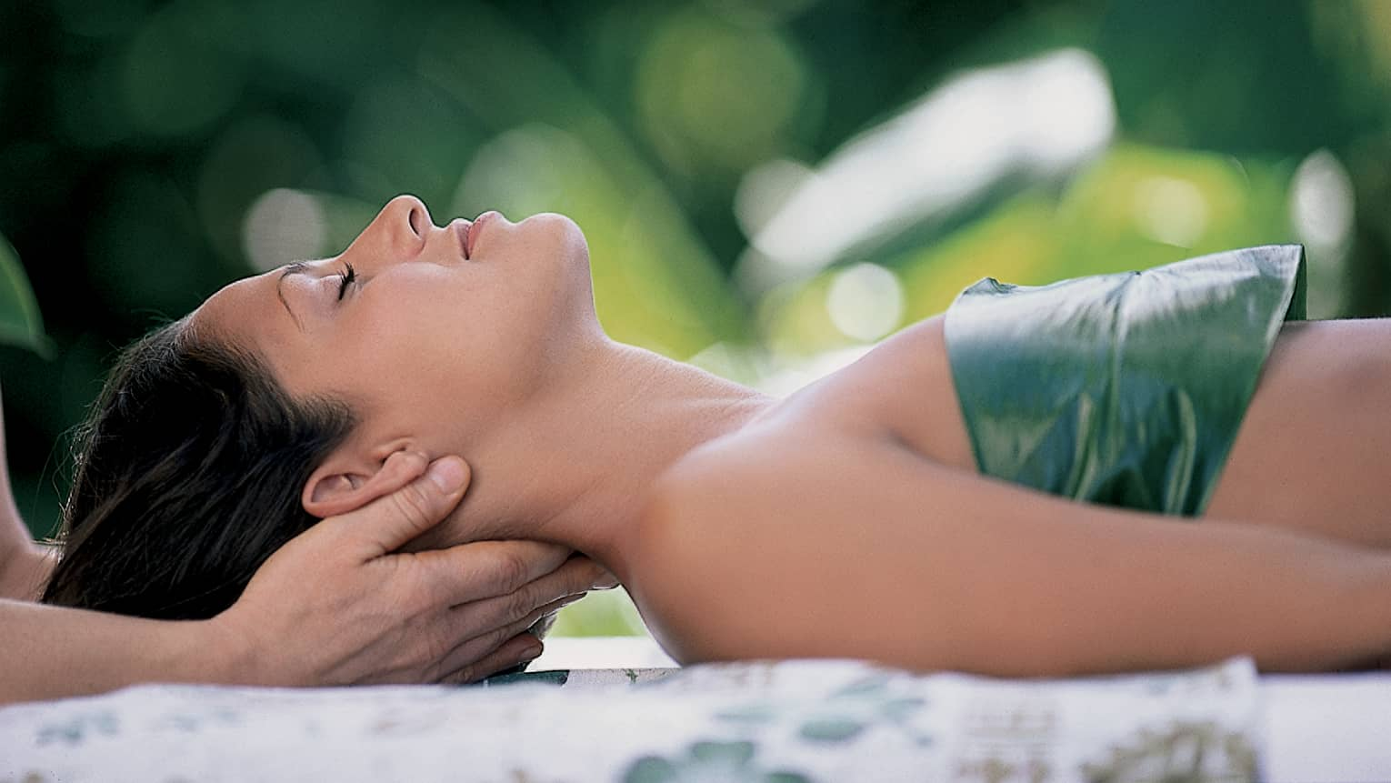 Woman with eyes closed lays on back on table with leaf over chest, hands massage her neck