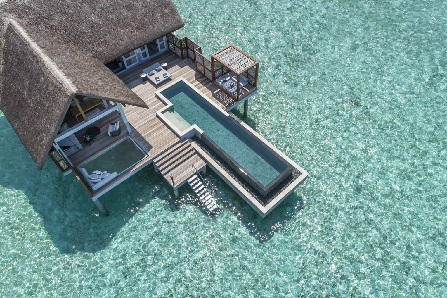 Aerial view of lure island villa with private pool and deck surrounded by crystal ocean