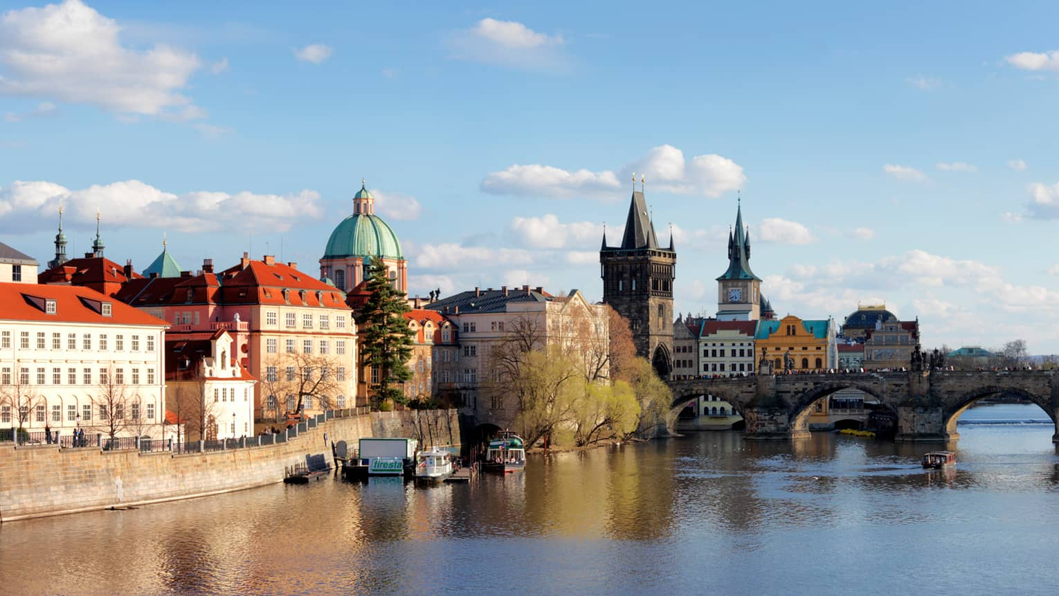 Prague waterfront on sunny day with historic Charles Bridge crossing Vltava River