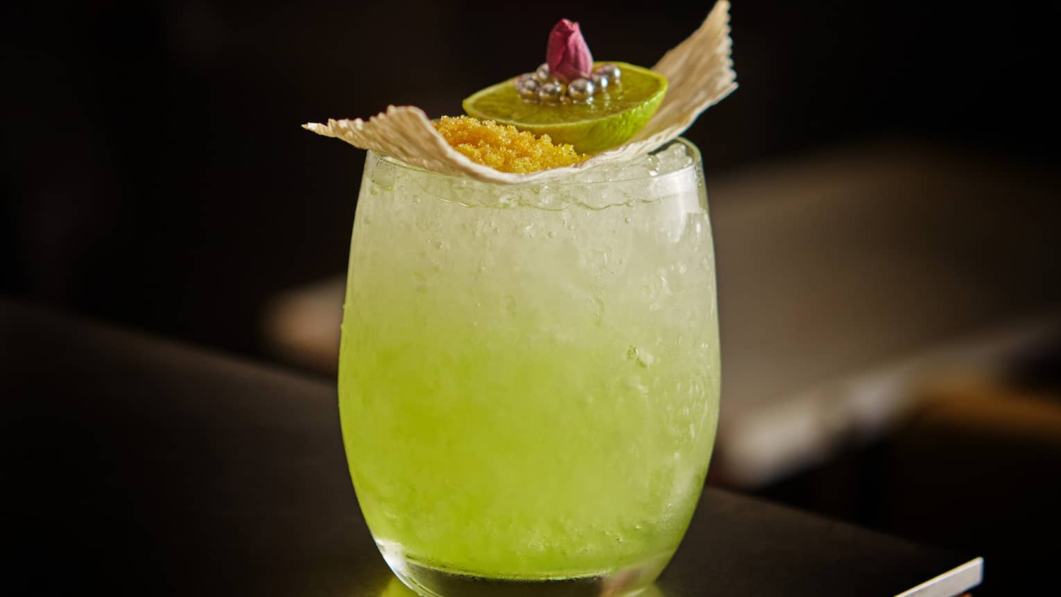 Bright-green Capri cocktail with lime garnish