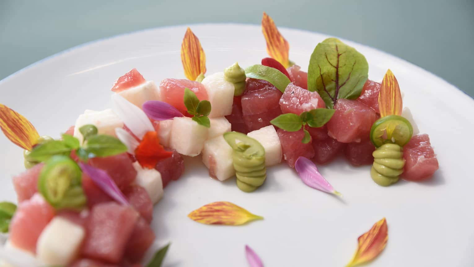 Diced local tuna garnished with jicama, avocado, edible flower petals