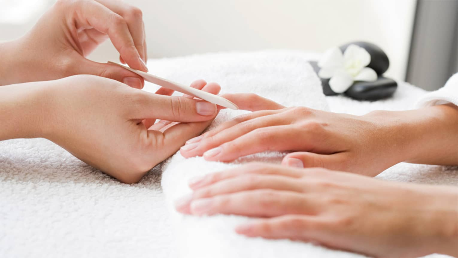 Close-up of spa attendant filing nails of woman's hands as they rest on white towel