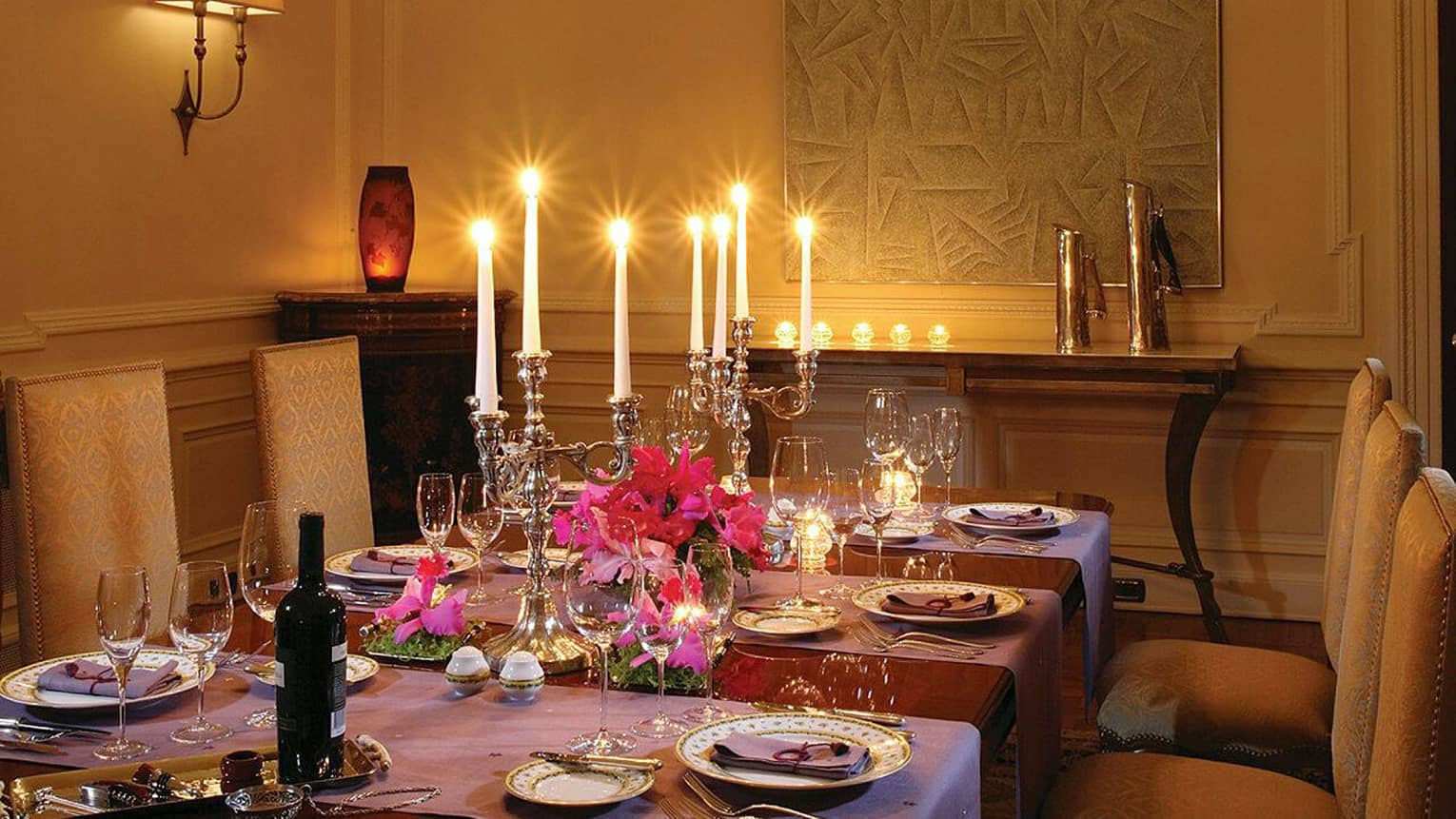 Elegant formal dining table with purple tablecloths, large silver candelabras with glowing candles, gold patterned chairs
