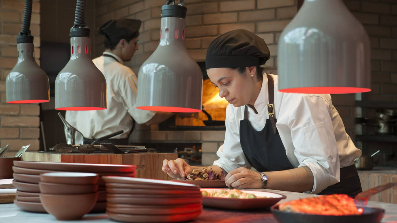Chef in black hat, apron garnishes dish under heat lamps in Elena Restaurant kitchen