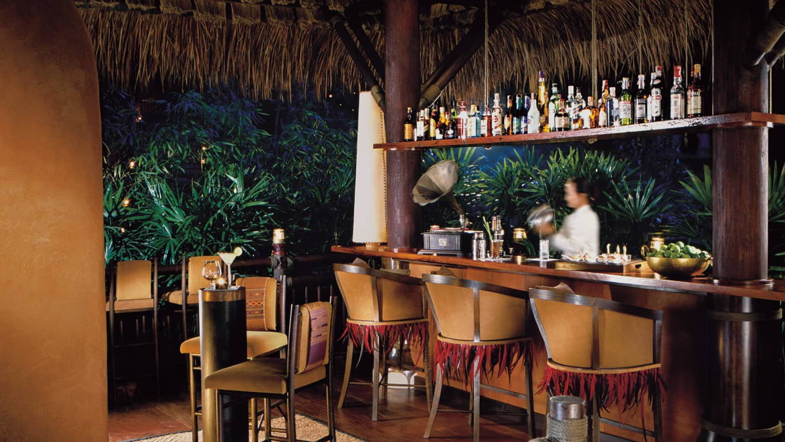 Bartender at Burma Bar with wood stools, tables under thatched-roof at night