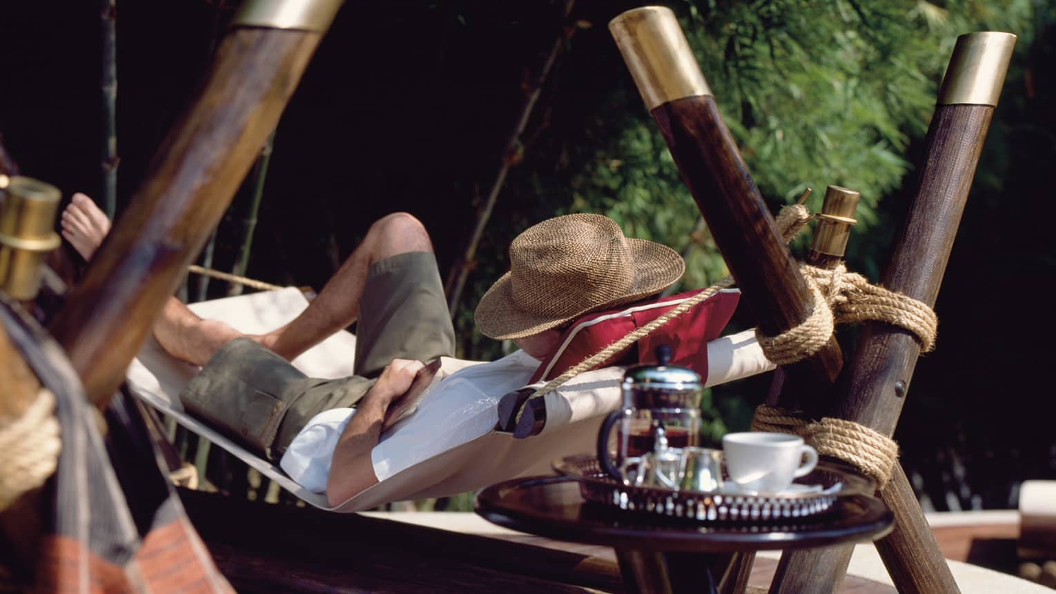 Man takes a nap in a handmade hammock with a straw sunhat shielding his face