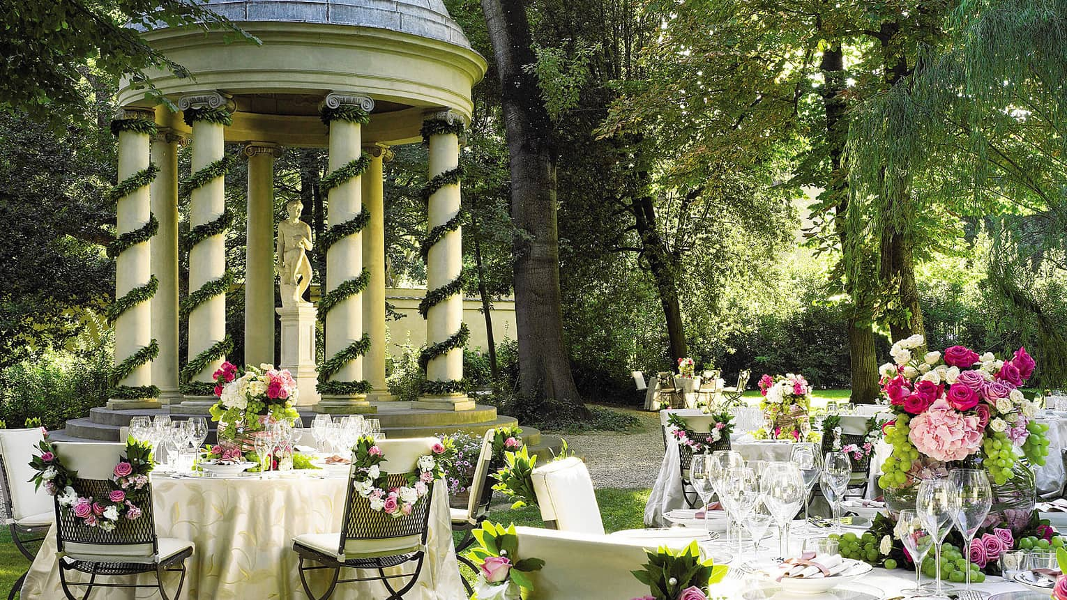 Garden reception, round, flower covered banquet tables by gazebo with white pillars