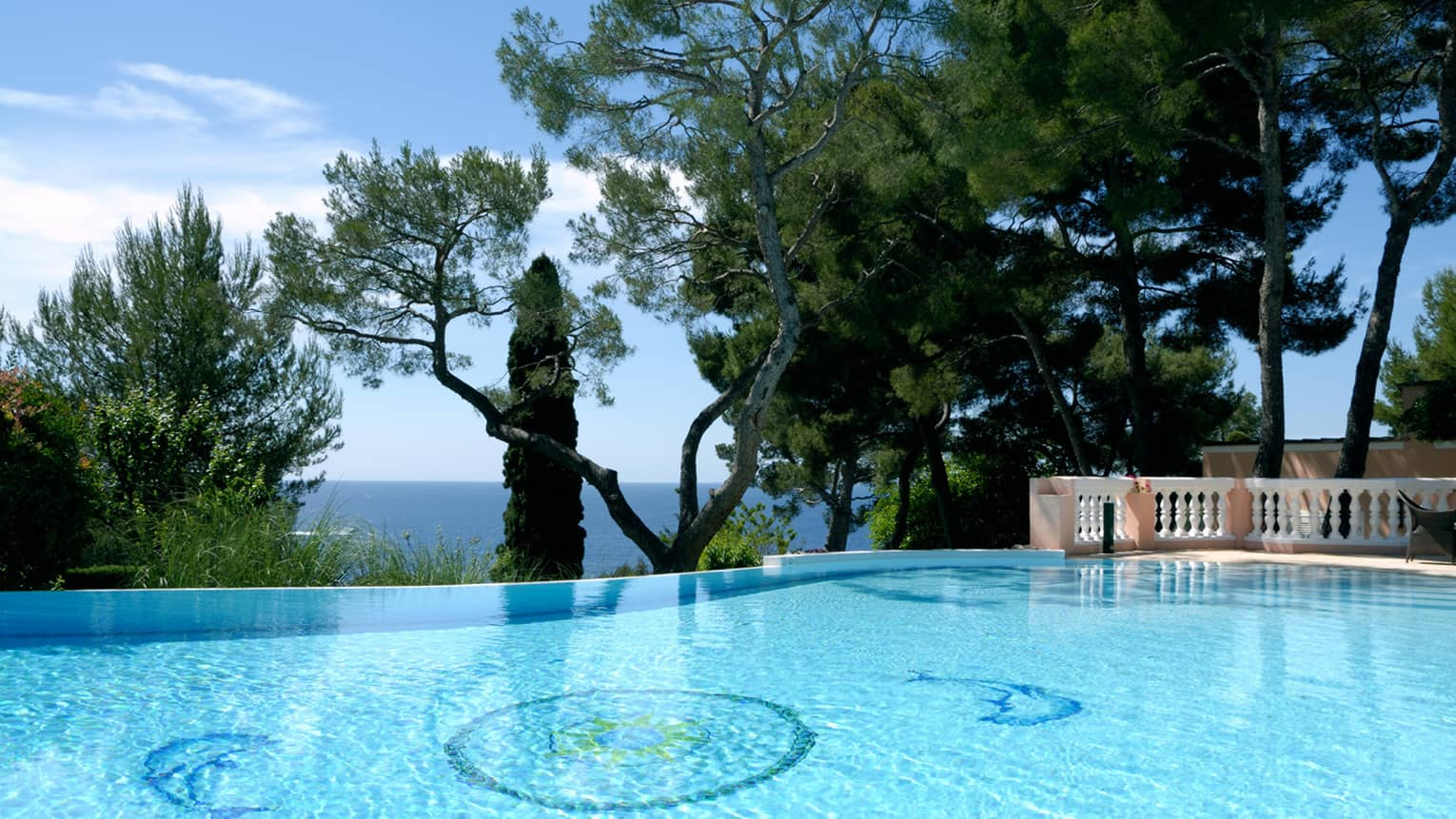 Blue outdoor swimming pool, trees, sea views