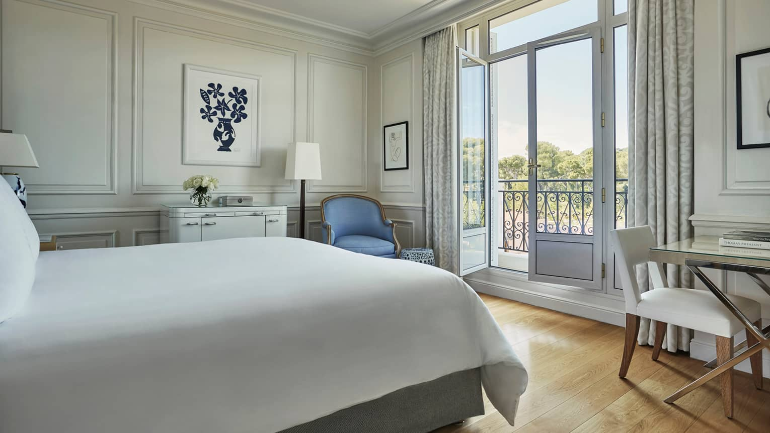 Superior Pinewood Room bed, blue armchair in corner by open French doors to balcony
