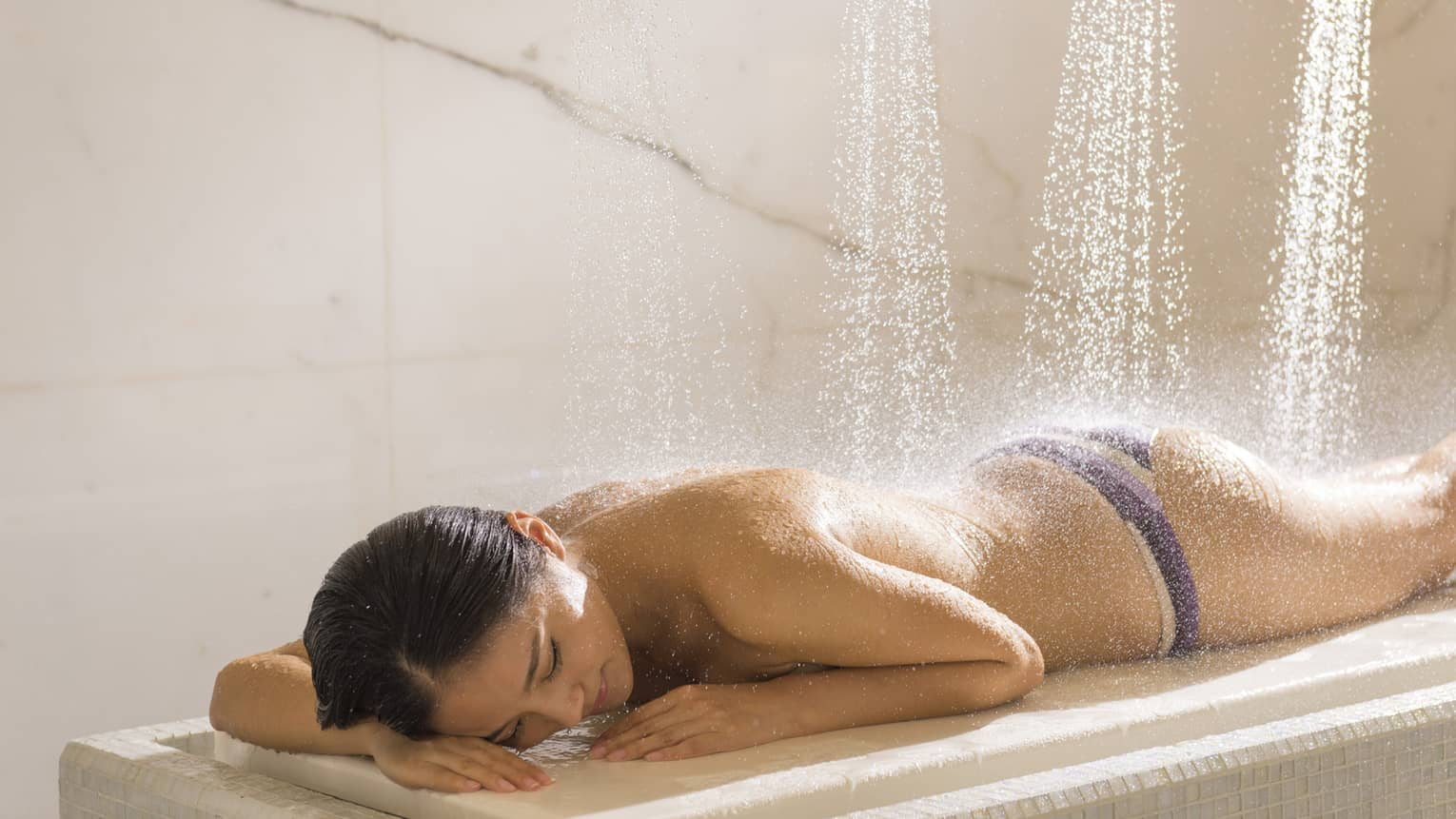 Woman lays face-down on table as Vichy shower waters fall on her back