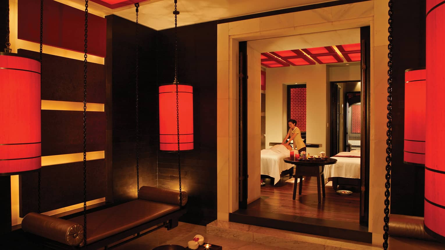 Spa staff gives massage on table behind doorway in dark spa with hanging red lanterns