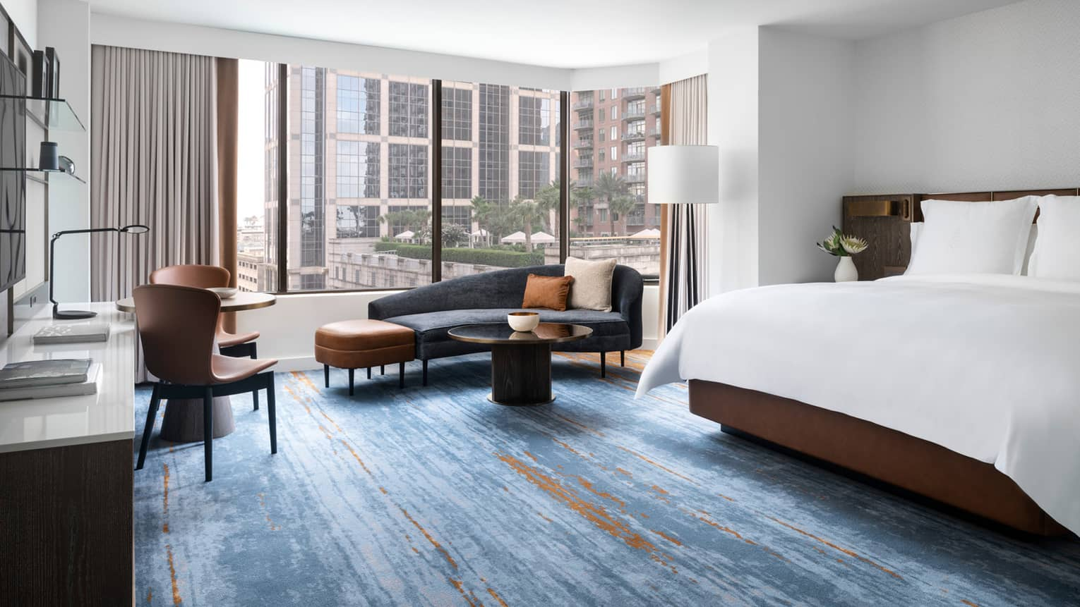 Hotel room with blue carpeting, king bed, dark blue chaise lounge, large windows