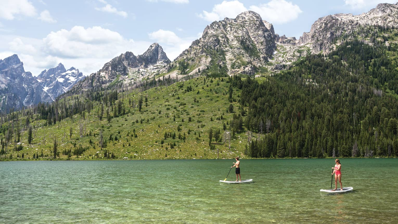 Two people on stand-up paddleboards on lake under mountain hills, trees, snowy peaks