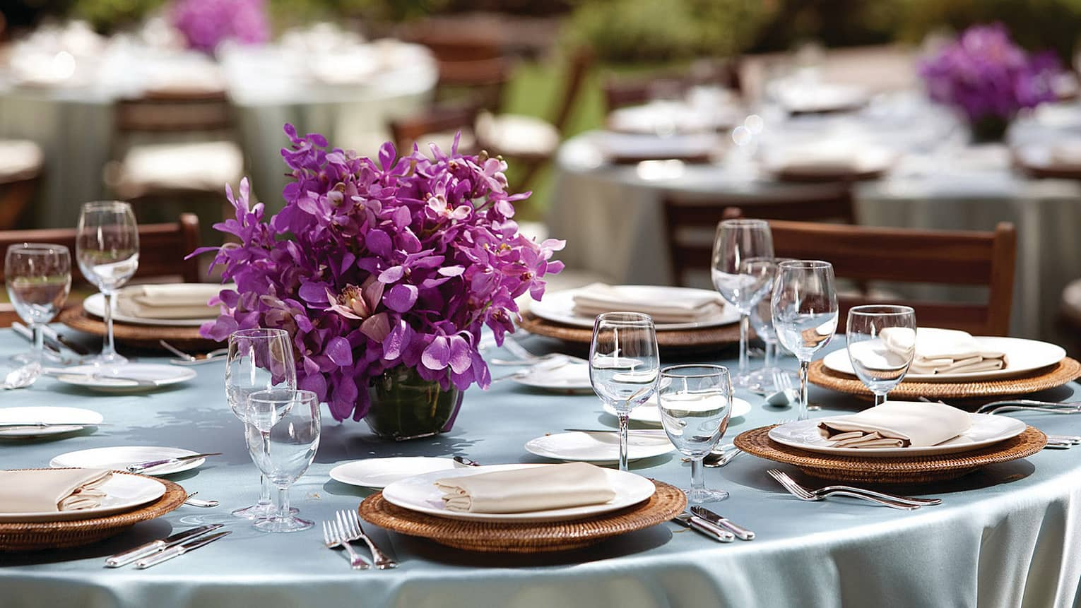 Close-up of round outdoor dining table with place settings, purple flower centrepiece