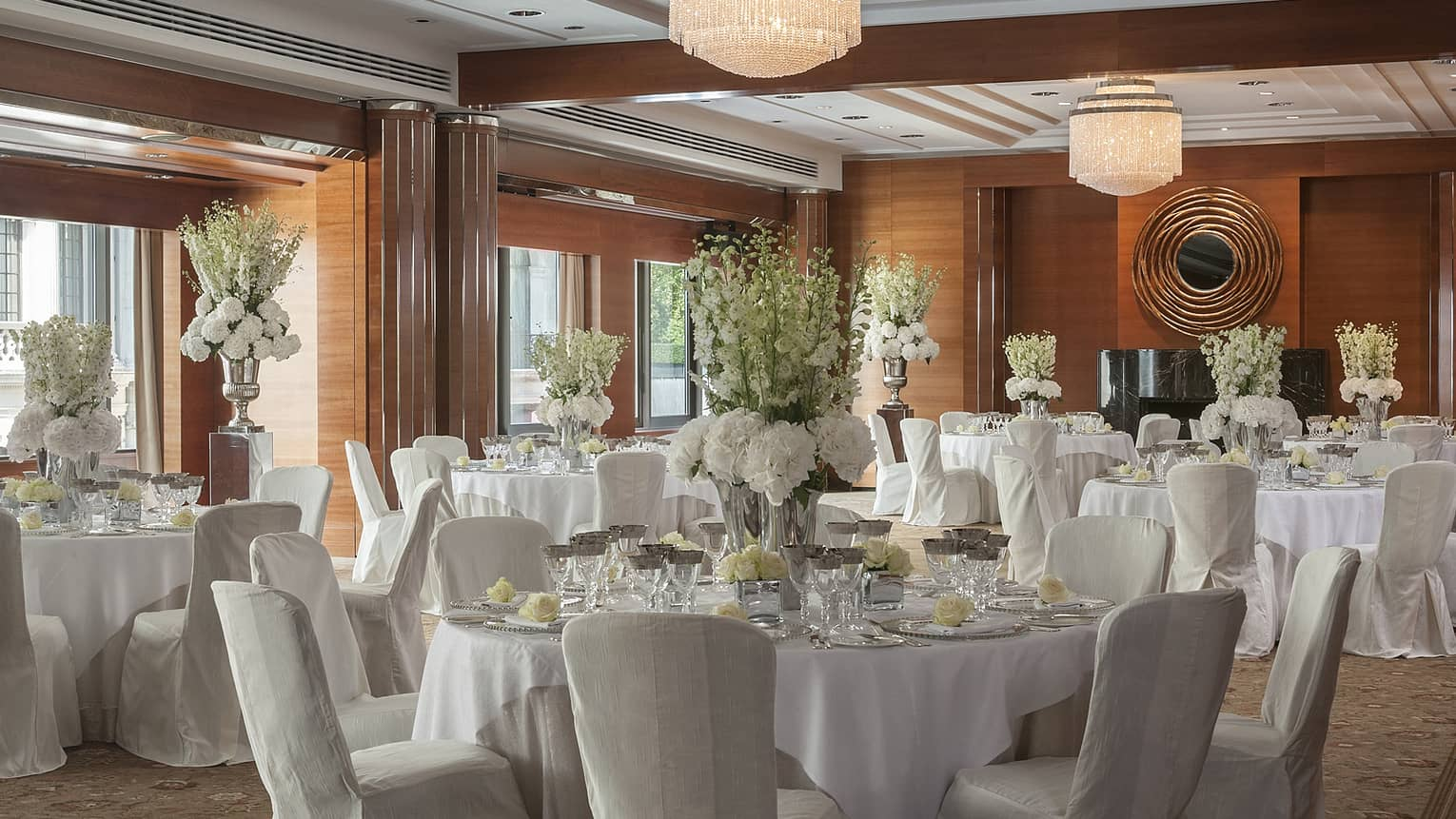 Sunny ballroom event with round banquet tables, chairs with white linens