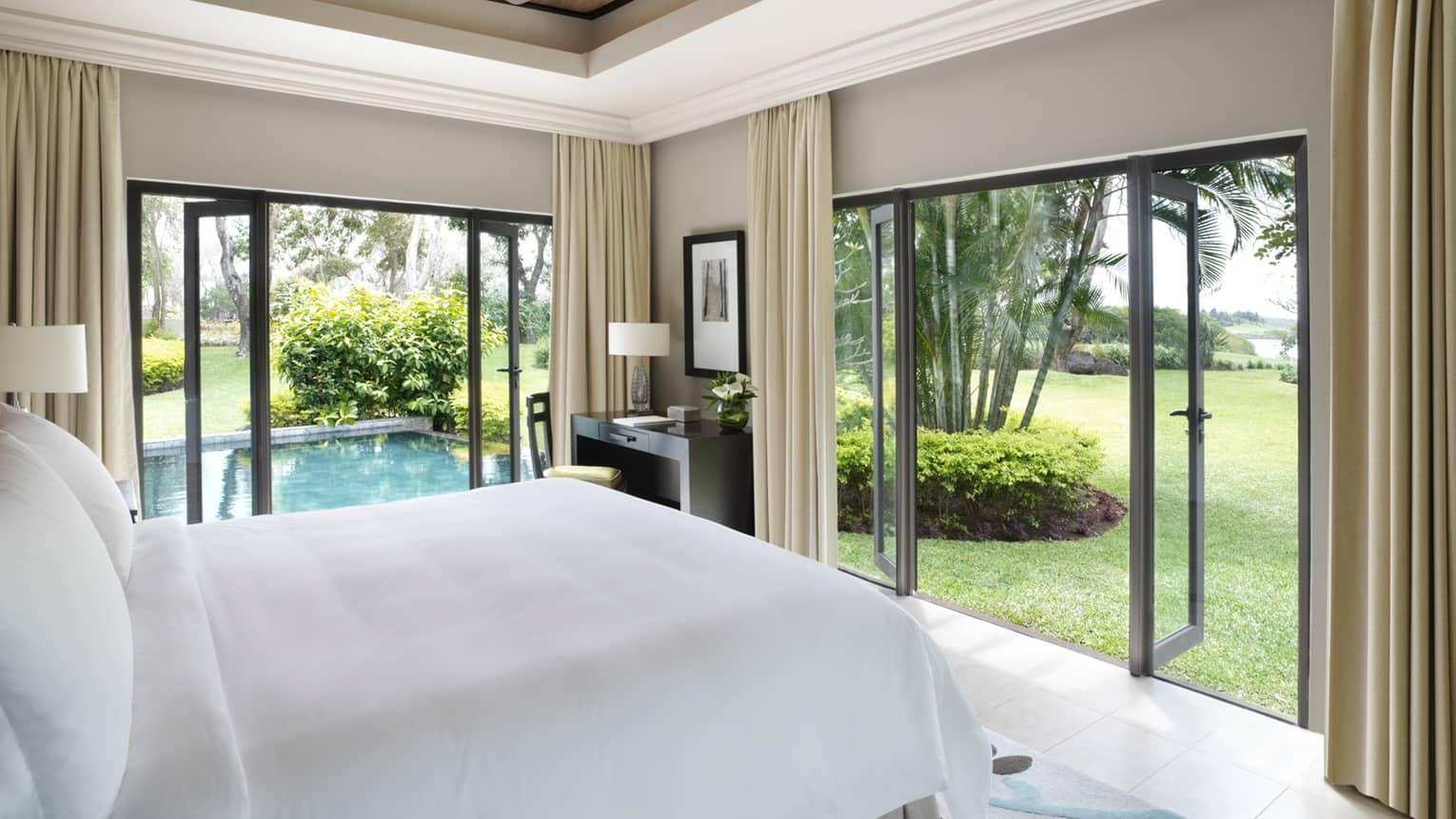 Deluxe Residence Villa side of bed with white linens, open corner patio doors, plunge pool