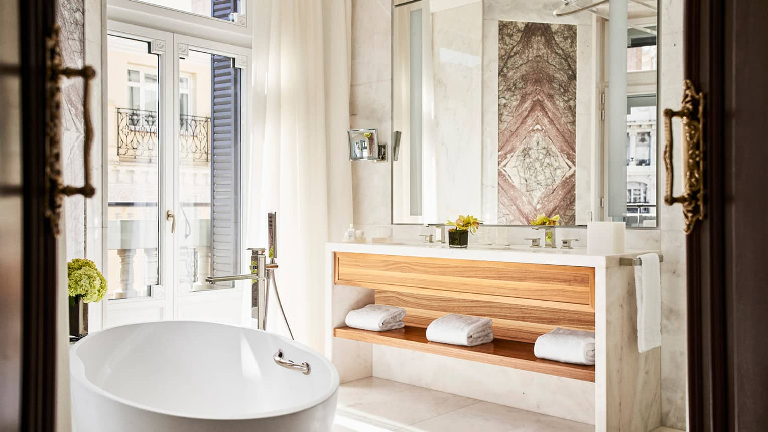Bathroom with window, white free-standing tub, wooden vanity, large wall mirror