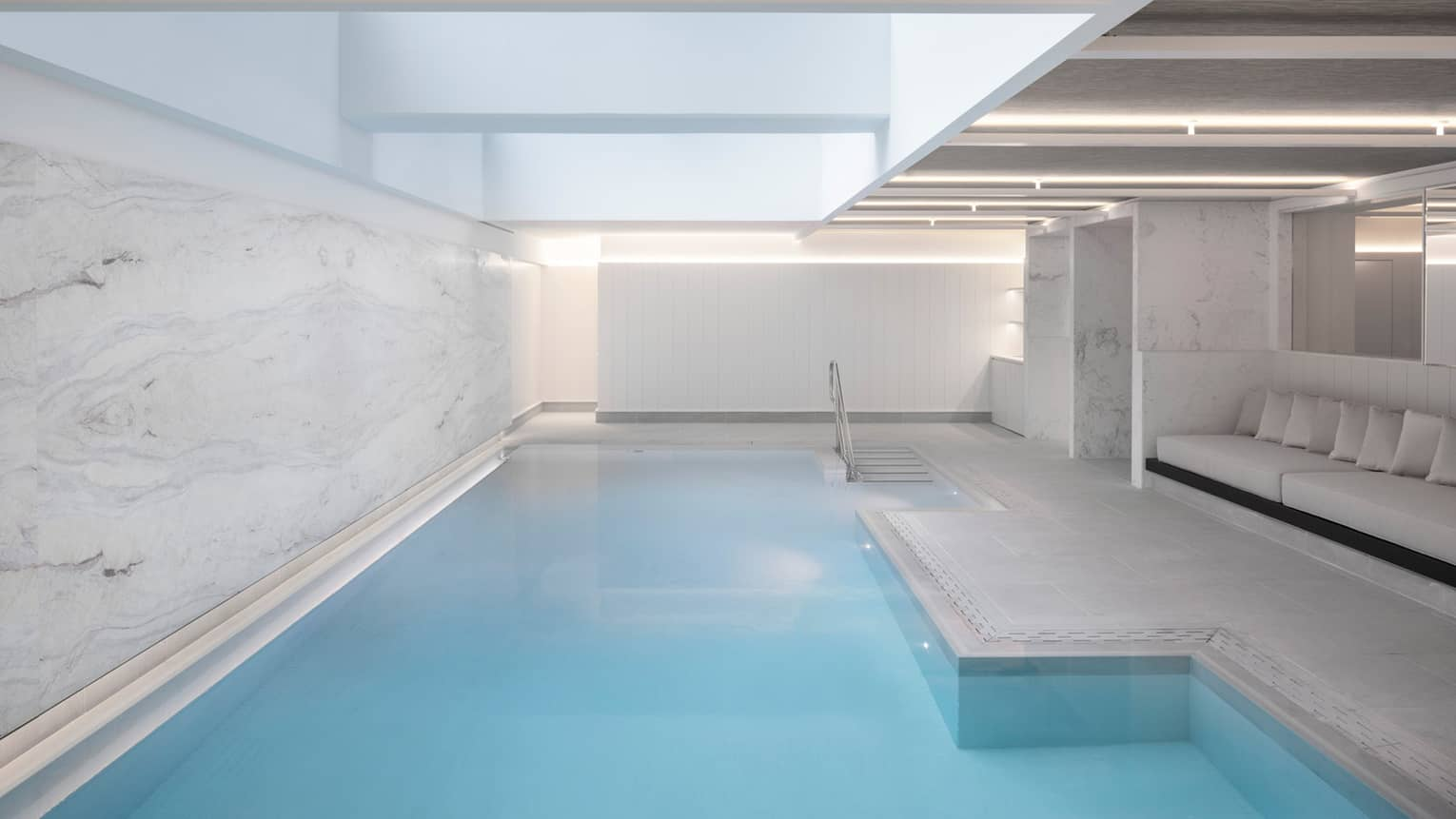 Indoor pool at spa, banquet of seating on one side, marbled wall on other