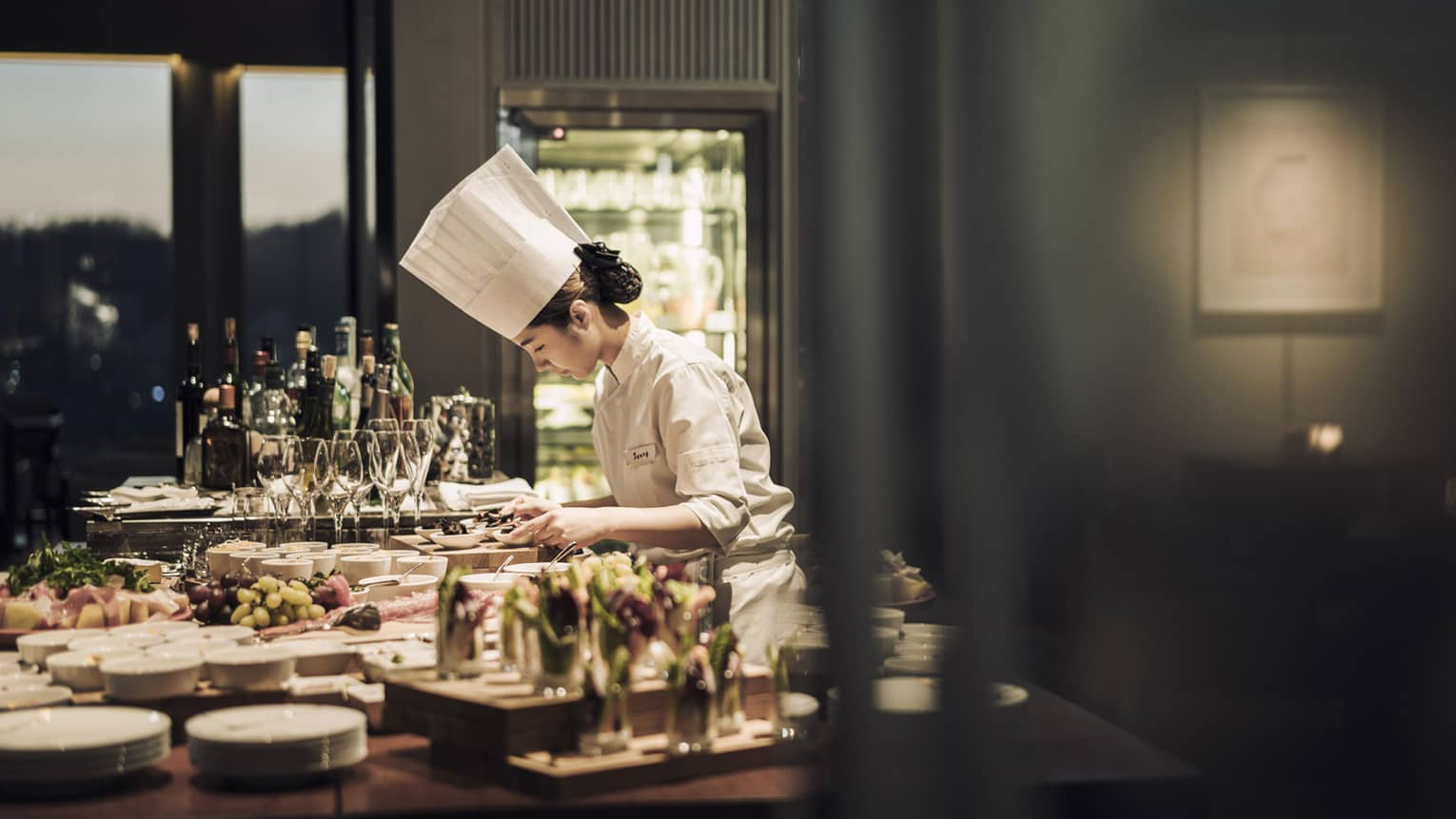 Chef wearing white uniform, hat stands garnishes appetizers on counter covered with dishes, meals