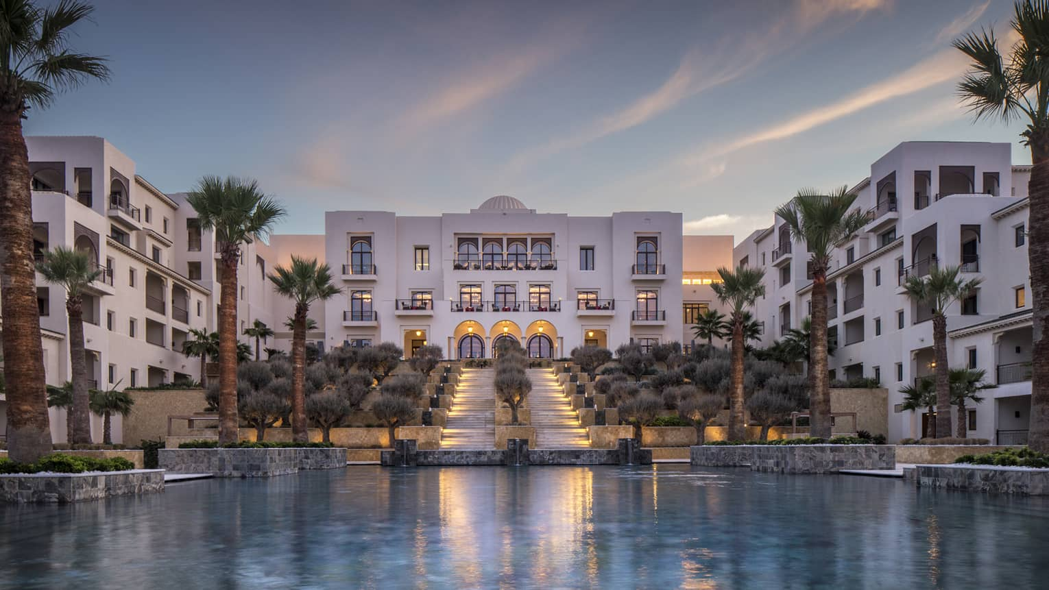 Four Seasons Hotel Tunis modern white buildings around pool, palm trees at sunset