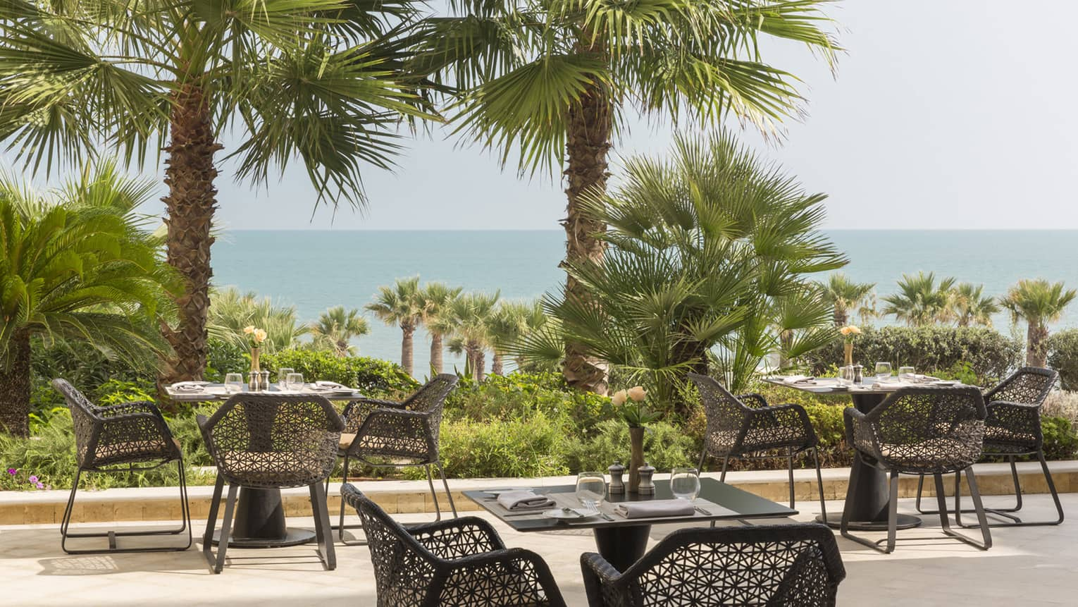 Black tables and geometric black chairs at outdoor bistro overlooking palm trees and ocean