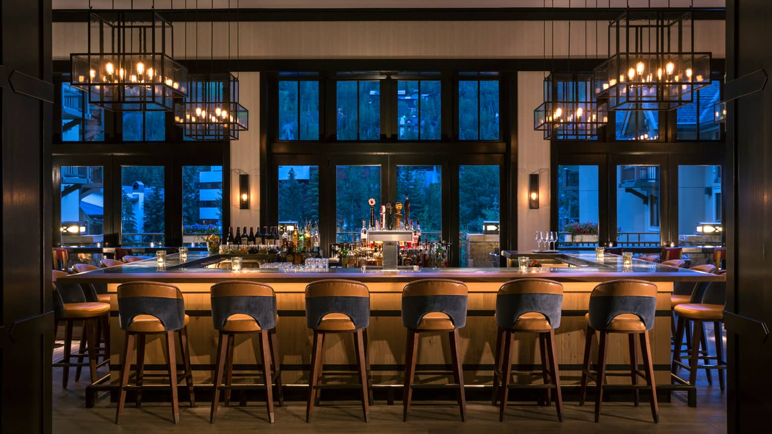 Dimly-lit bar at dusk lined with retro-style wood stools, lantern chandeliers above, large windows