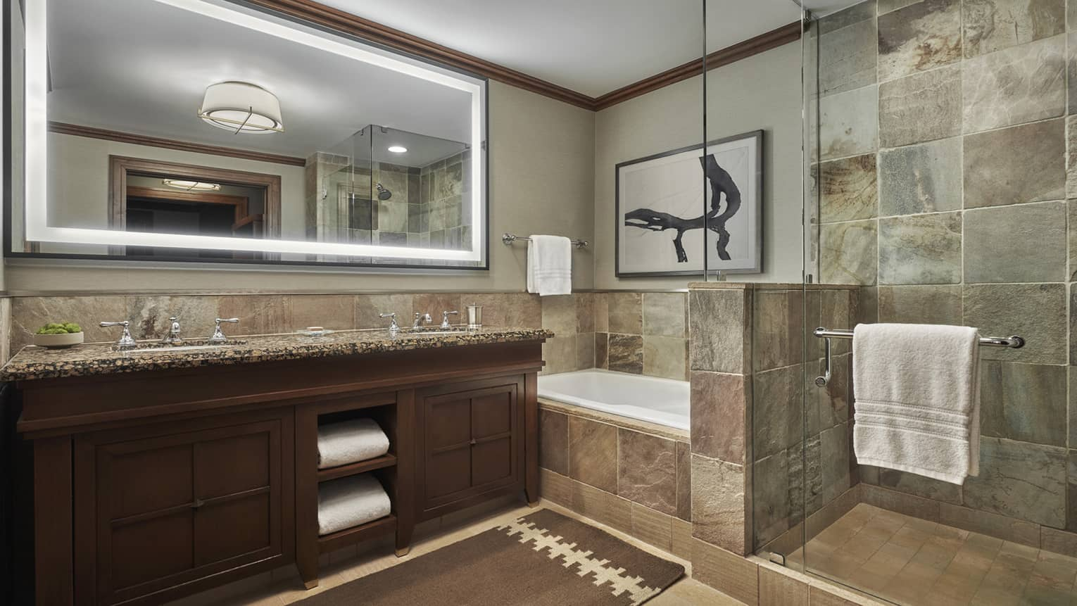 A tiled bathroom, with a double vanity, large lighted mirror and a shower and tub separated by a glass partition