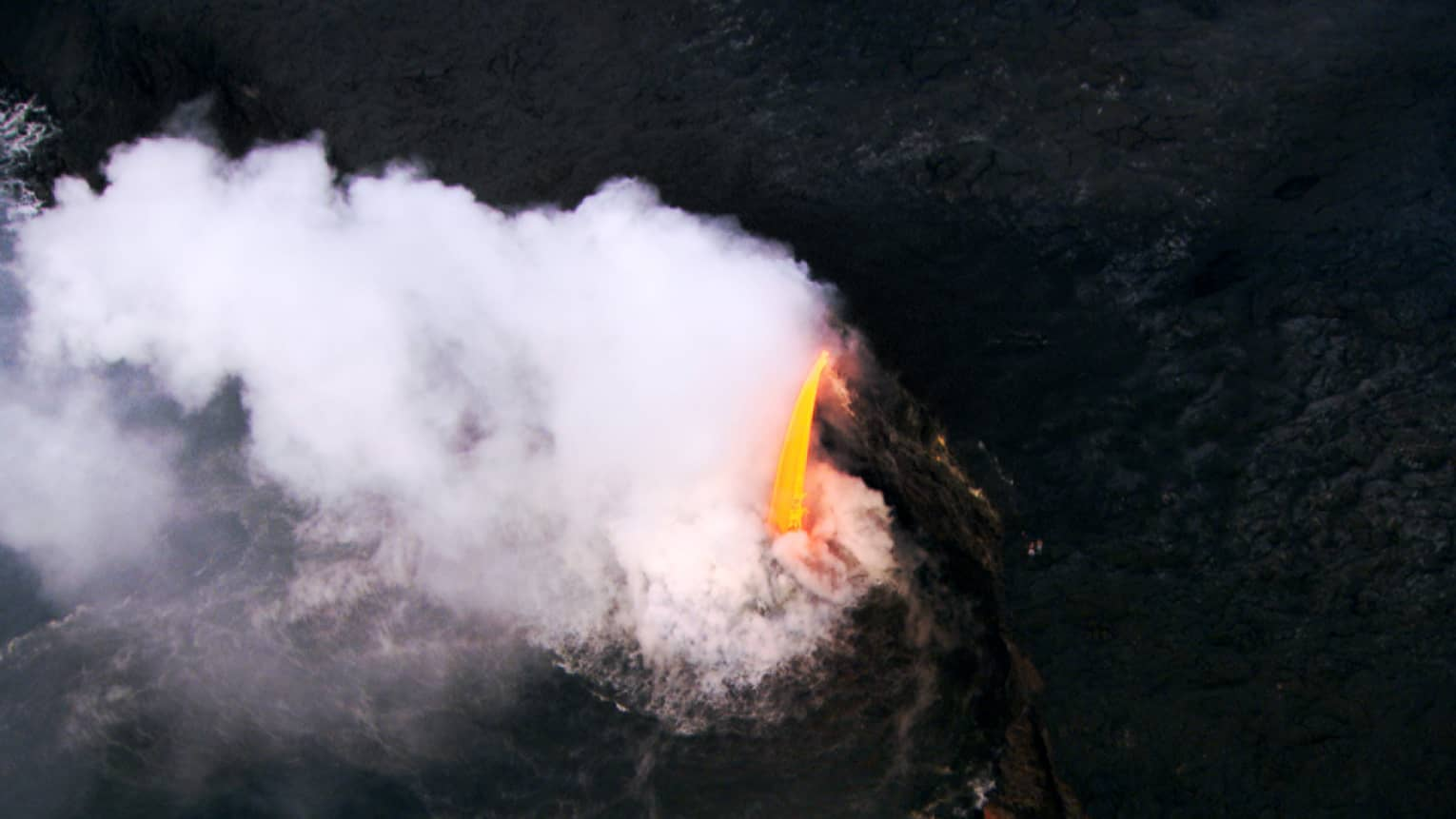 Aerial view of steam rising around black lava rock, stream of hot orange lava