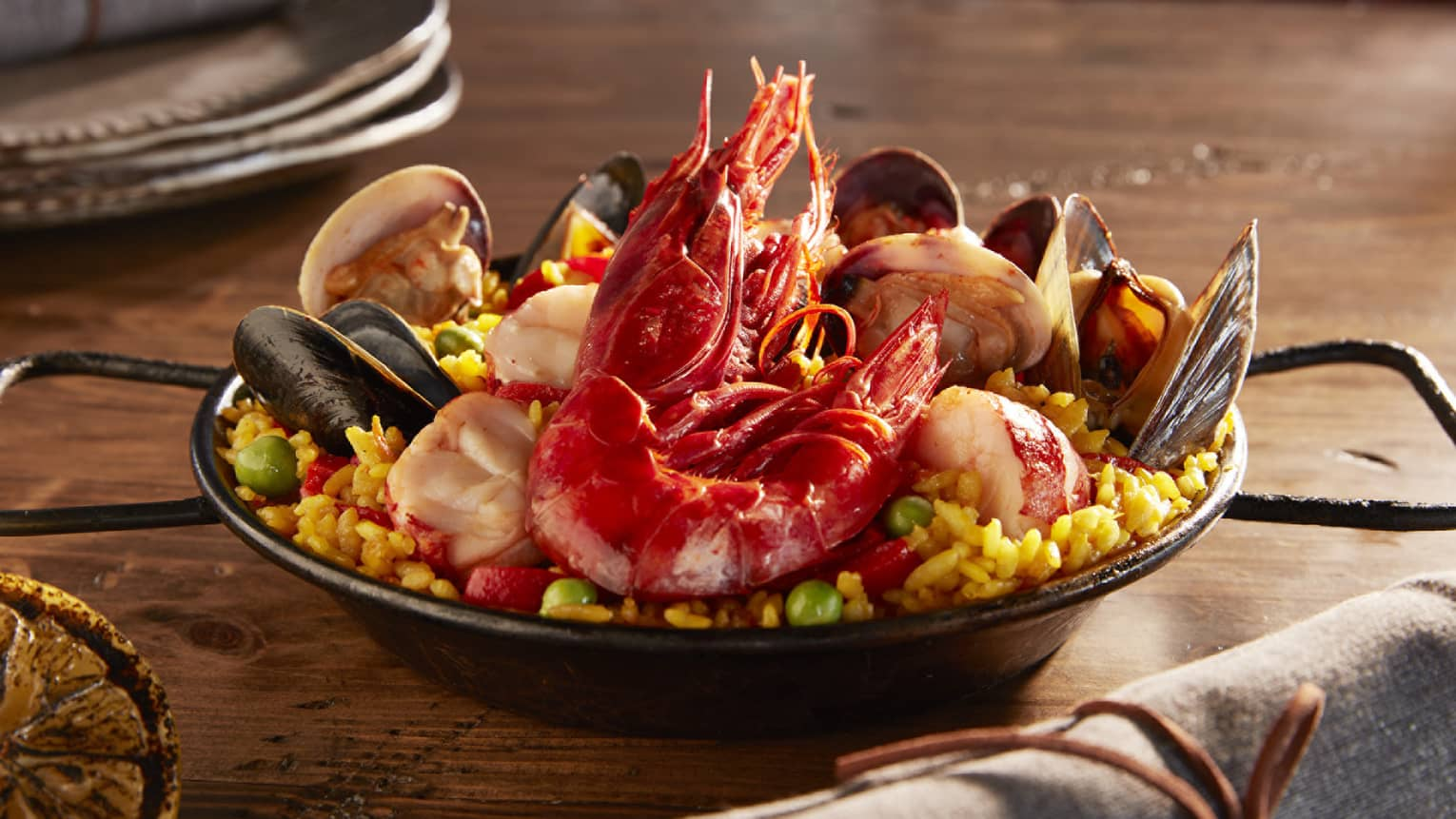A dish consisting of corn, clams and shrimp sits on a wooden table