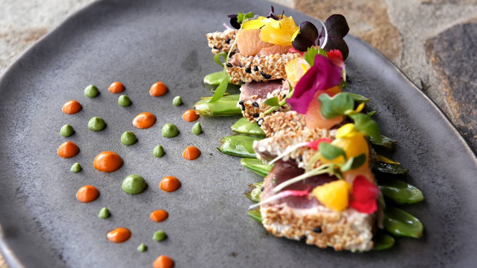Sesame-crusted tuna topped with colourful edible flowers and green & orange dots
