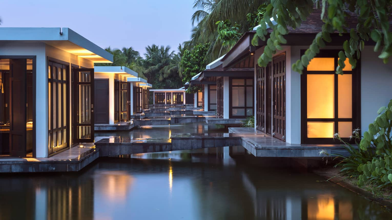 Spa villas over lotus pond connected by marble tile walkways at dusk