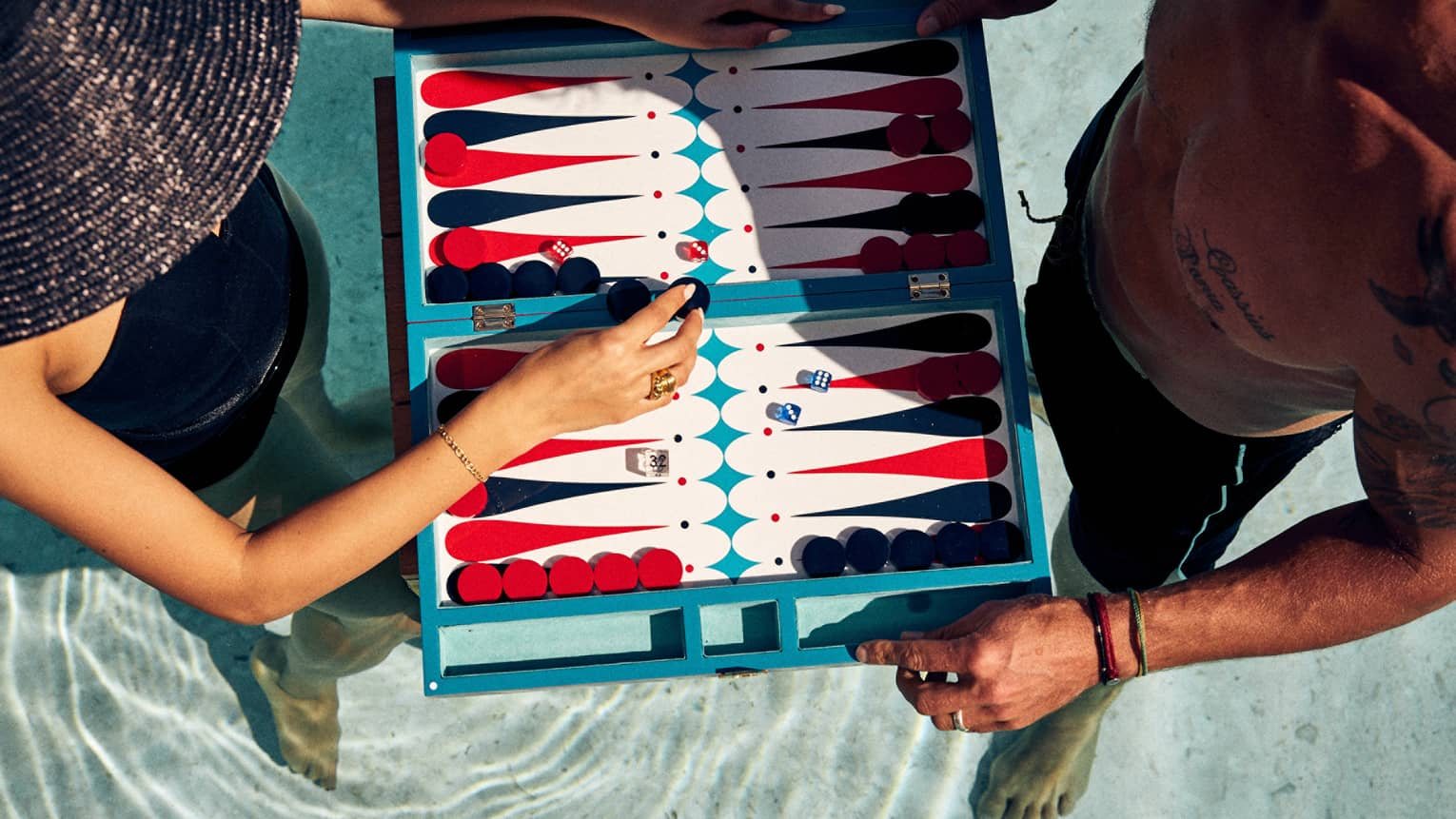 Aerial shot of man and woman in a pool, playing a floating game of backgammon