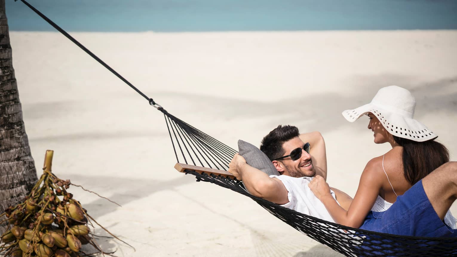 Sand beach, woman wearing sunhat sits on edge of hammock where smiling man relaxes