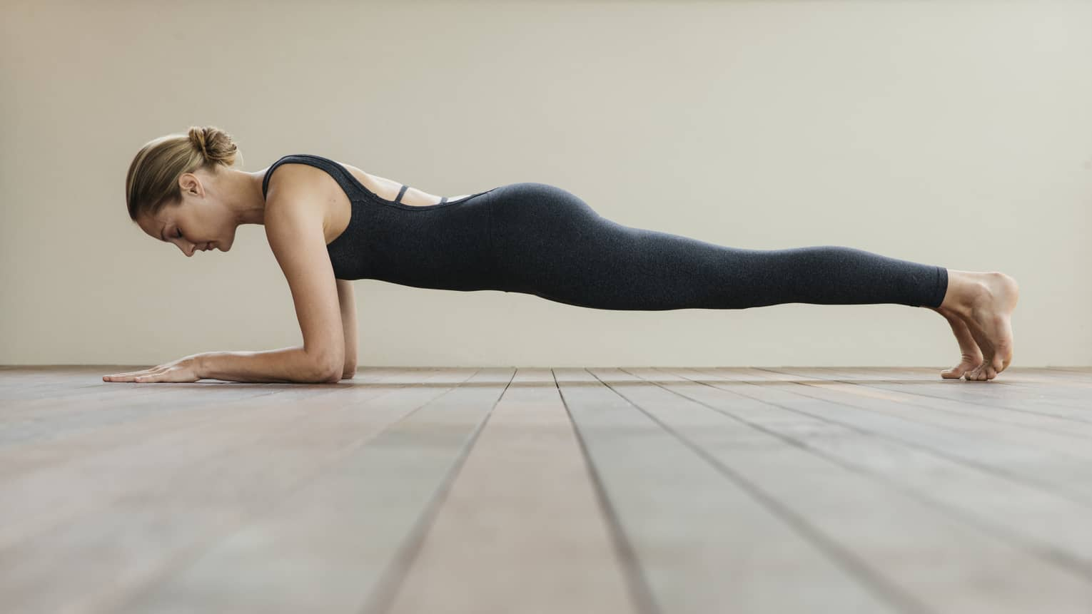 Woman wearing black exercise suit balances above floor in plank pose