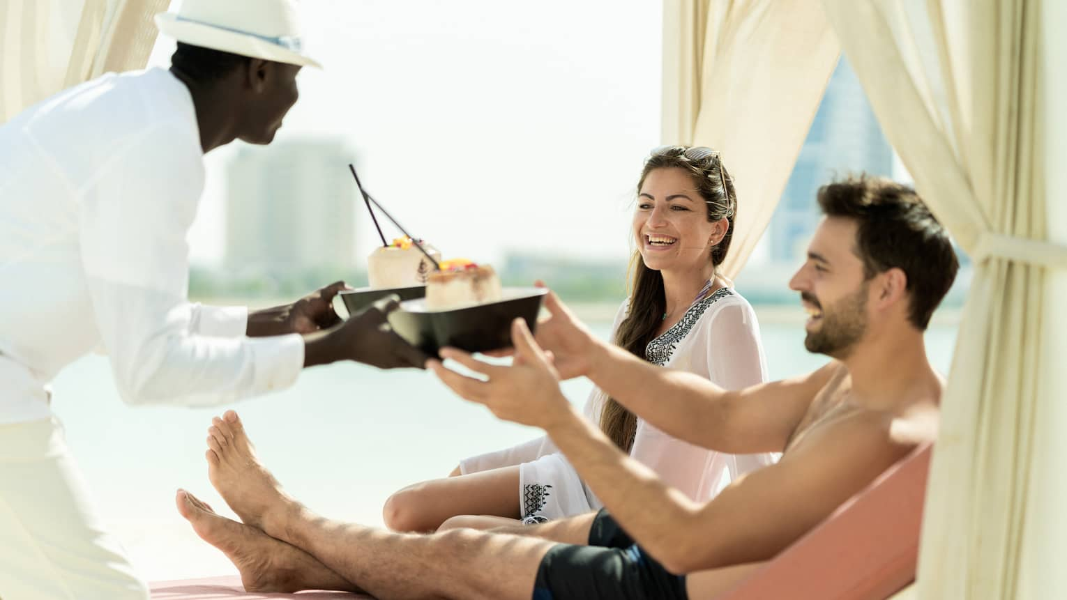 A four seasons staff hands two dishes to a man and woman as they lounge poolside