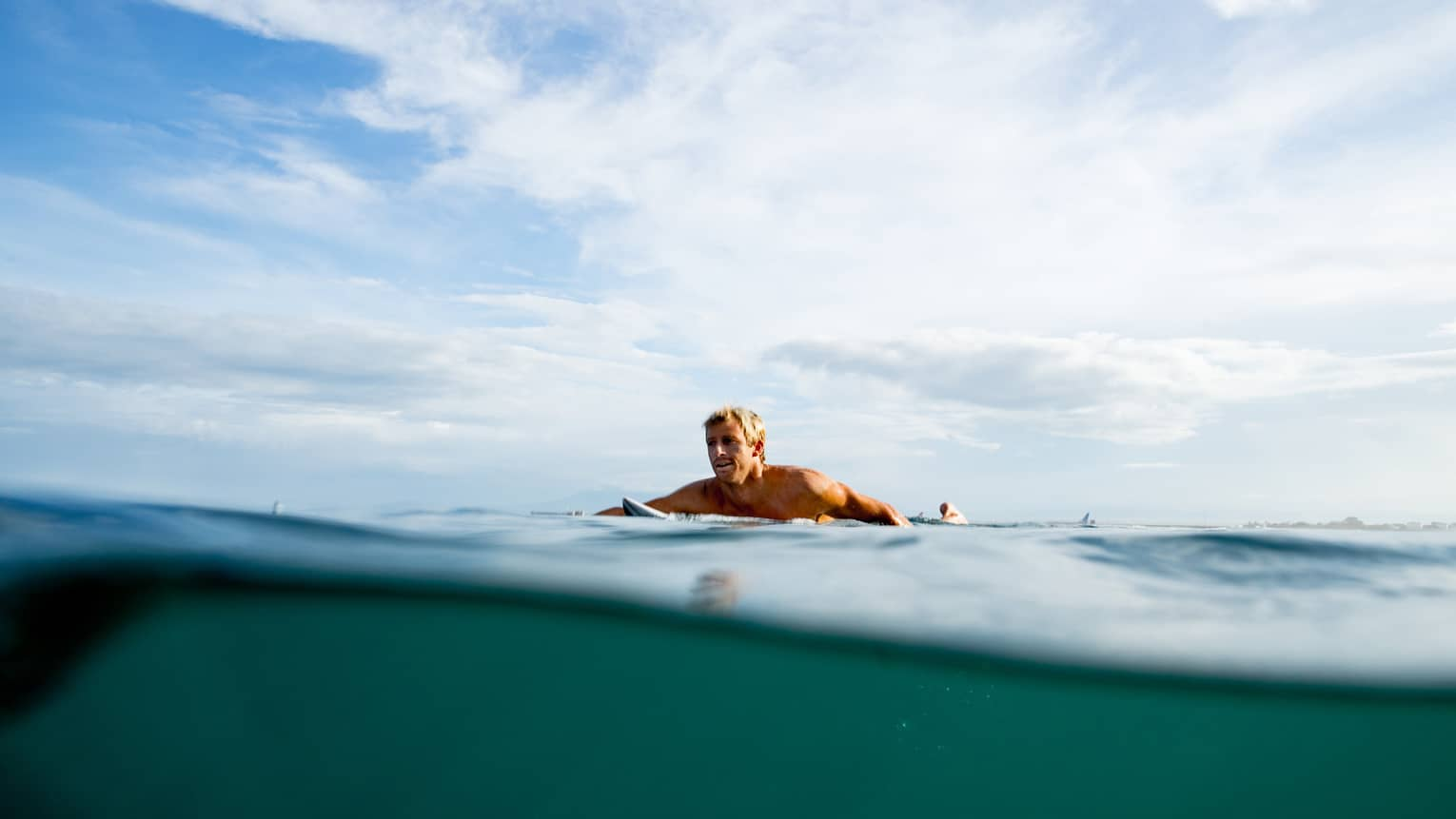 A guest swims out to surf on the water in Bali