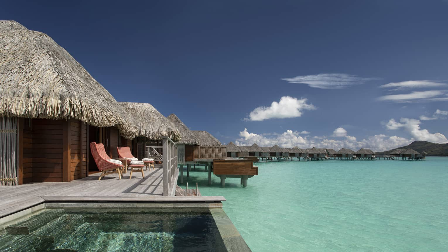 View of plunge pool and clear-blue lagoon from the deck of Two Bedroom Water Bungalow