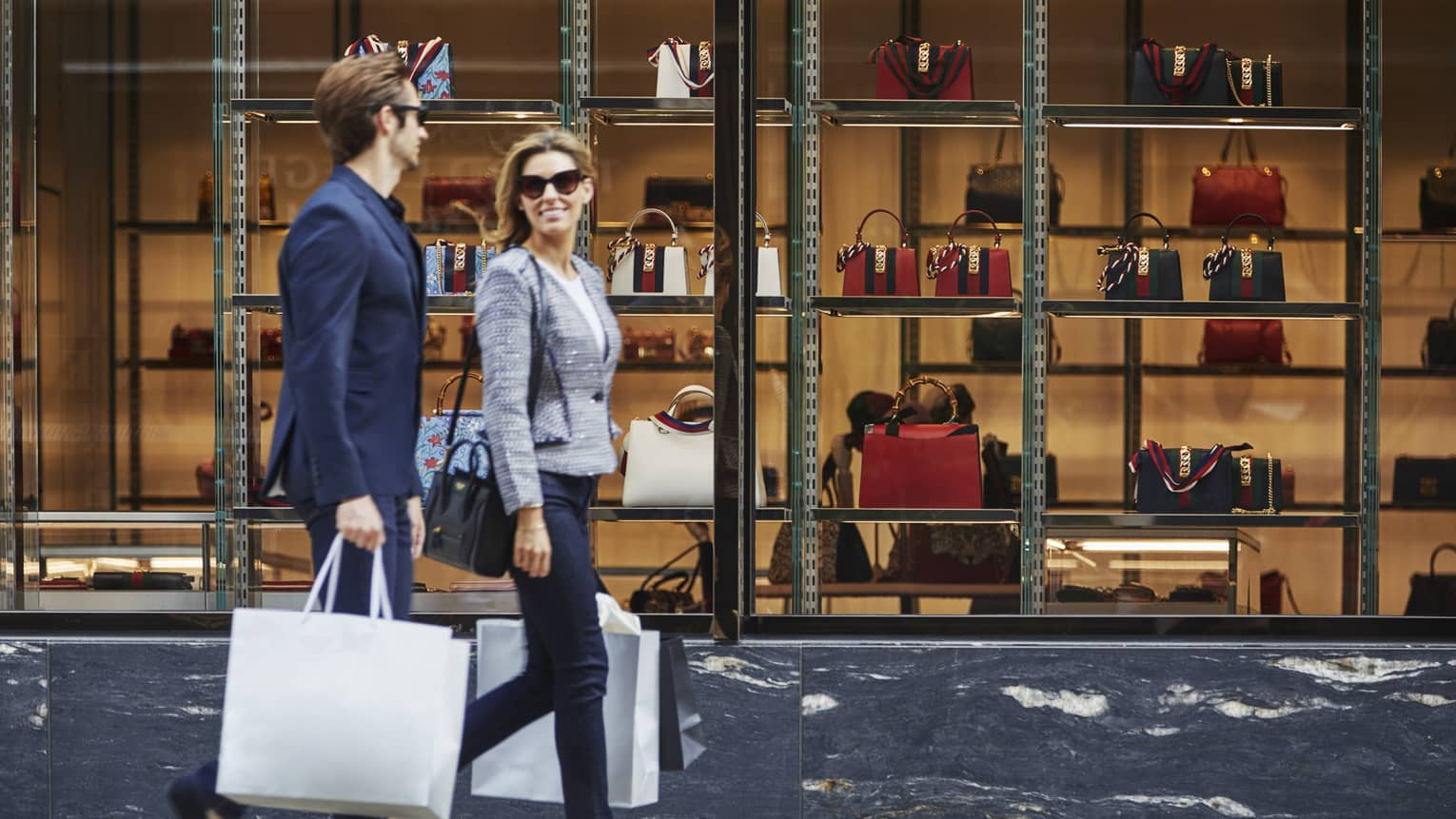 Man and woman in suit jackets, sunglasses hold shopping bags, walk by large store window with designer purses on display