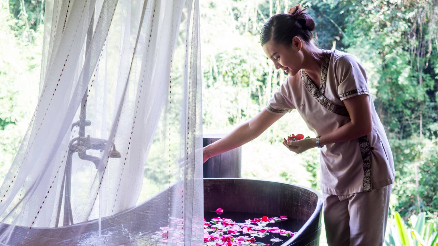Hotel staff drops colourful flower petals in free-standing copper bathtub draped with sheer white net