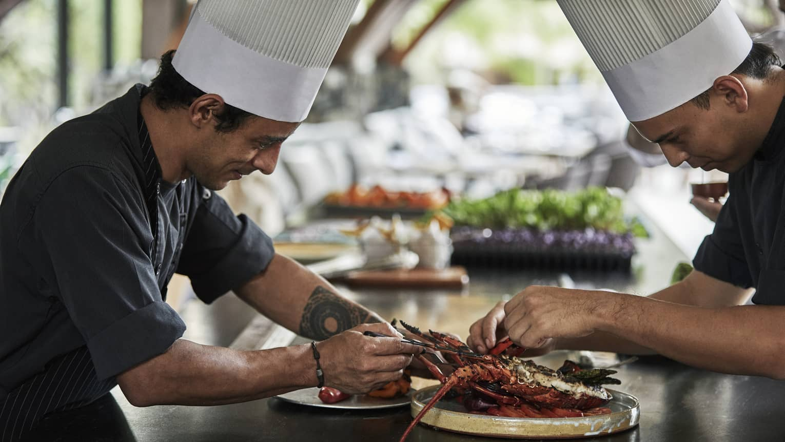 Two chefs in uniform assemble grilled lobster entree on long kitchen counter