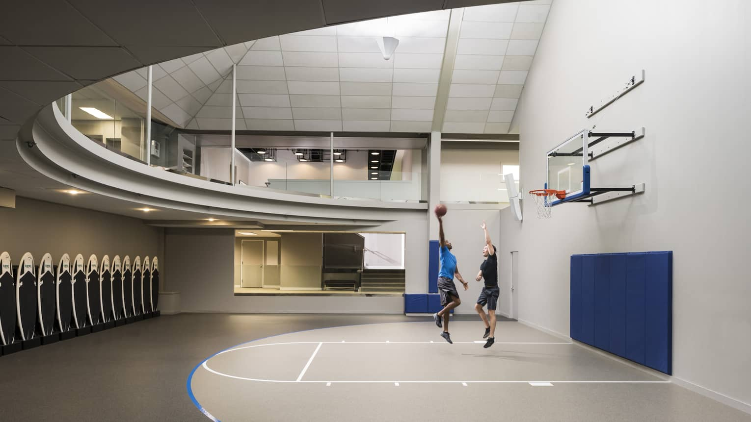 Two men play basketball on small court under modern curved ceiling