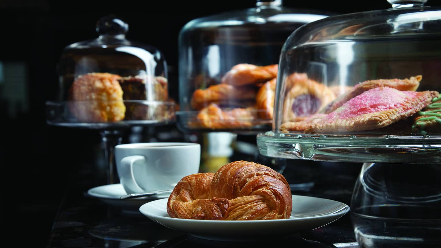 Croissant on plate by small coffee cup, breakfast pastries in glass displays