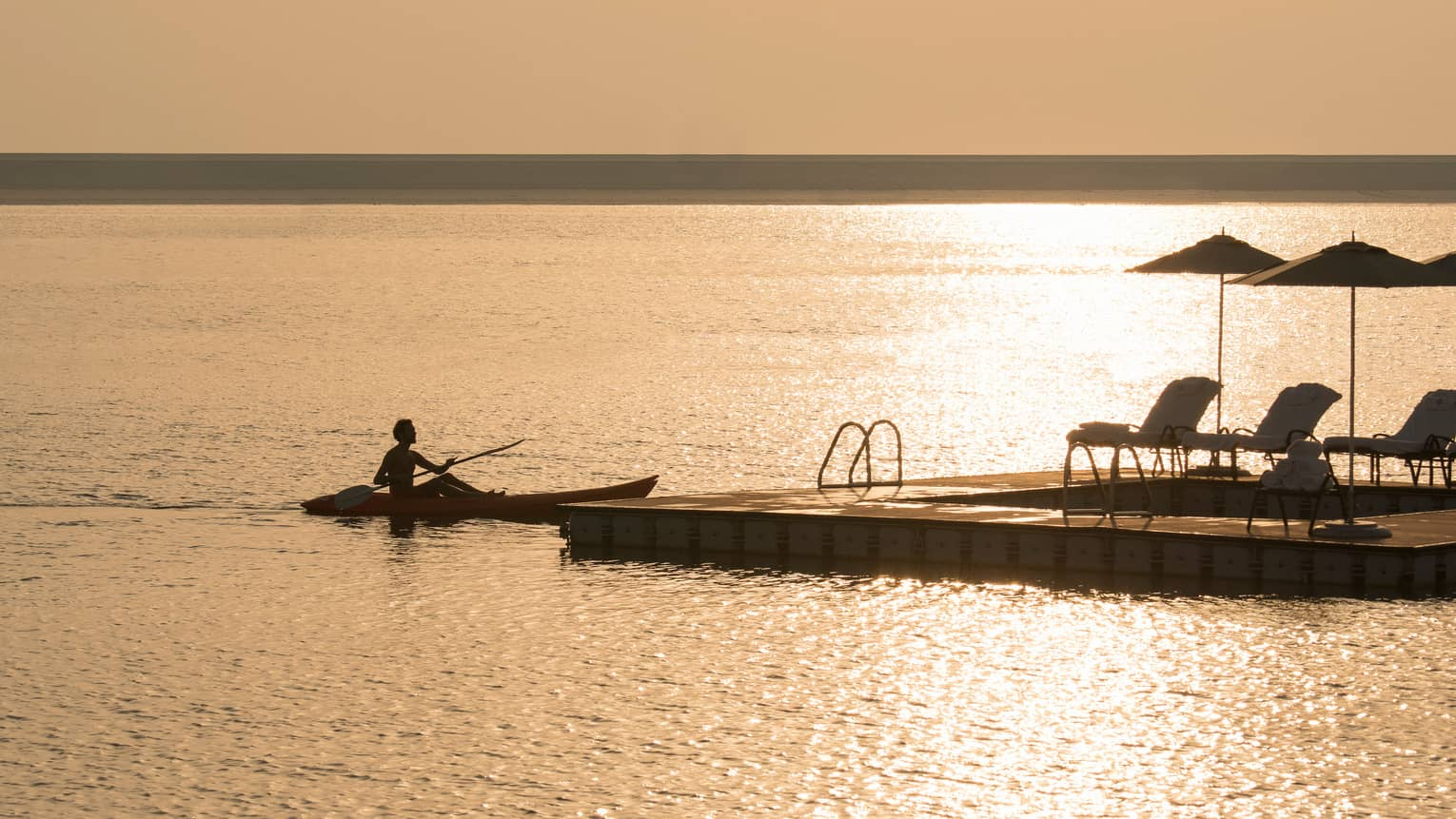 Silhouette of person in kayak with paddle on water in front of dock with patio chairs, umbrellas at sunset