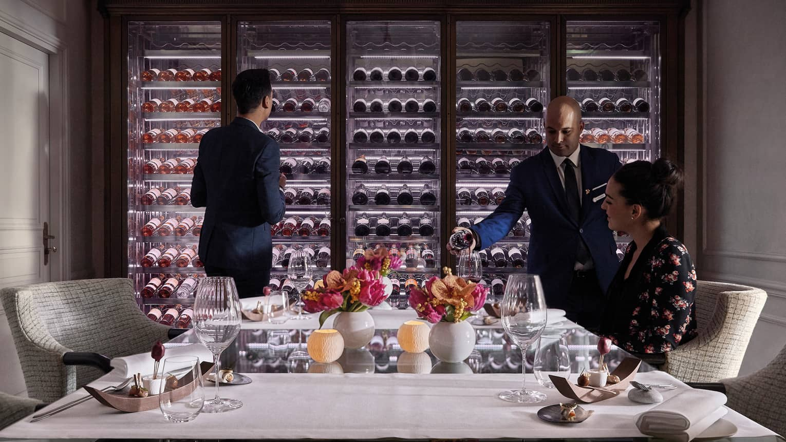 Man scans glass cellar as waitstaff pours wine in glass for woman at table