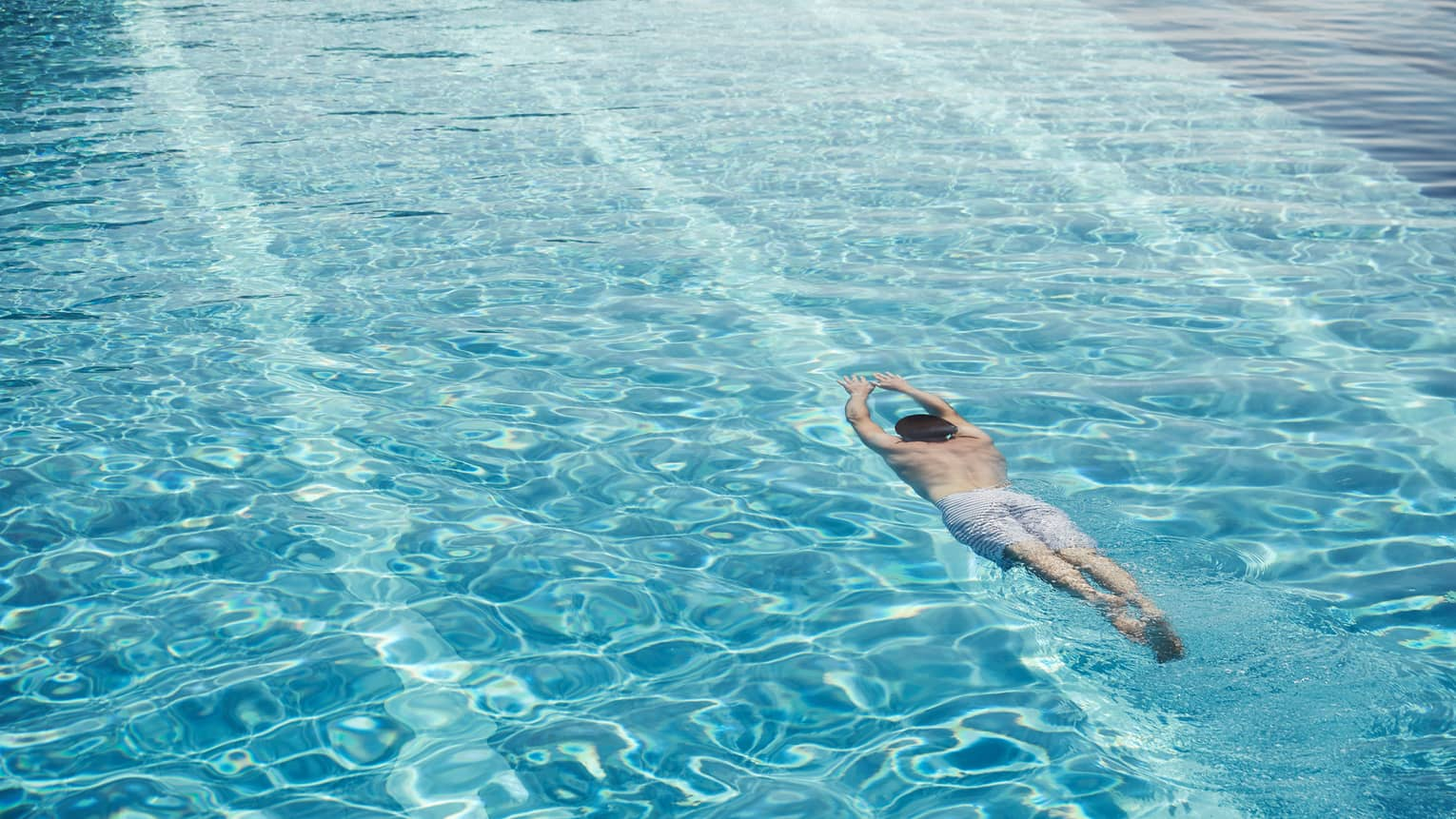 Man in swim shorts with arms outstretched dives underwater in blue swimming pool