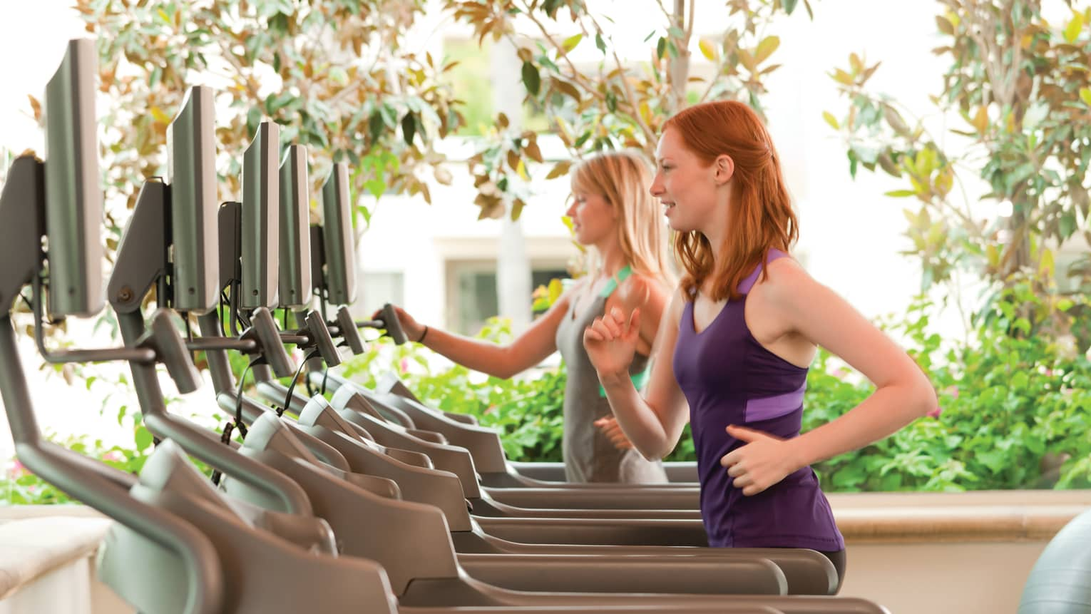 Two women run on treadmills in sunny outdoor Fitness Centre
